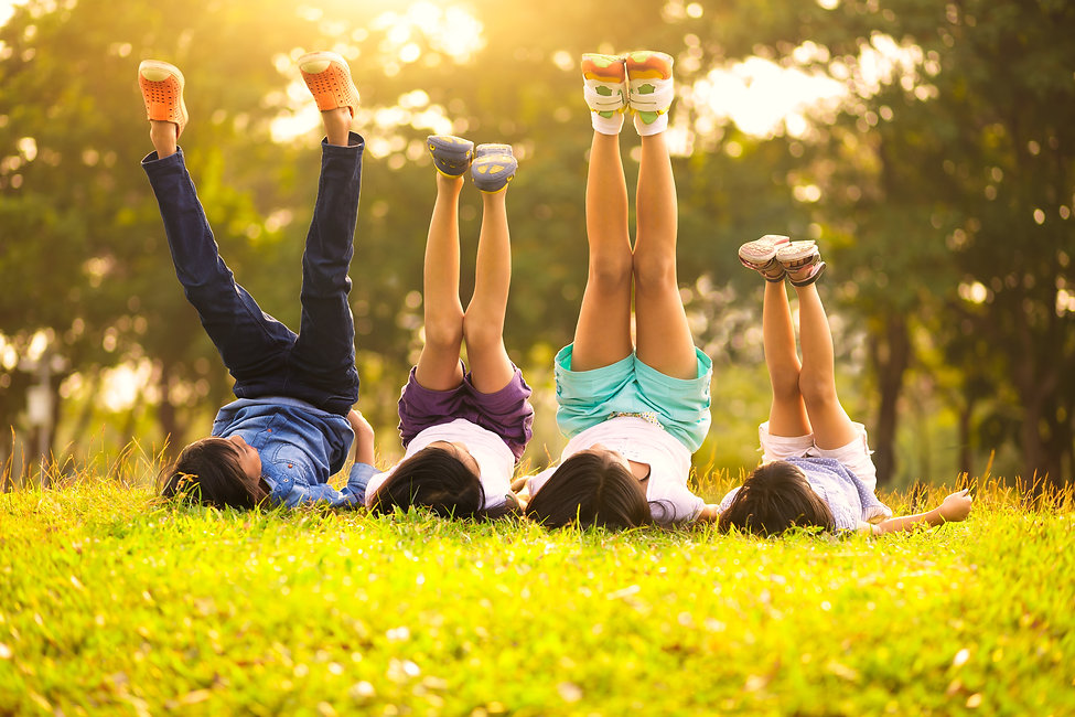 Group of happy children lying on green grass outdoors in spring park.jpg