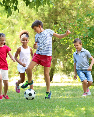 Cute children playing football in park.jpg