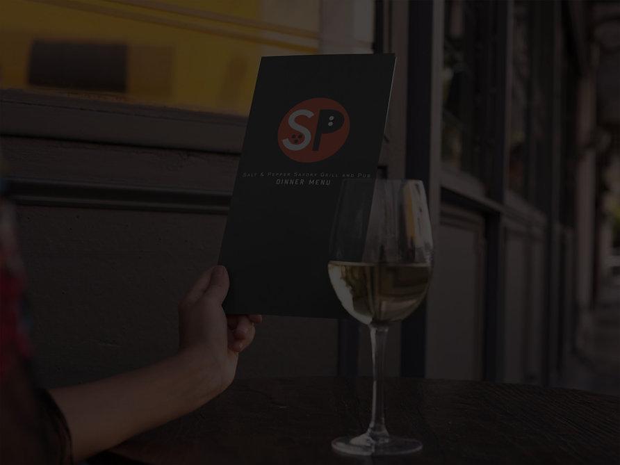 Mockup of Salt & Pepper Pub dinner menu next to glass of wine