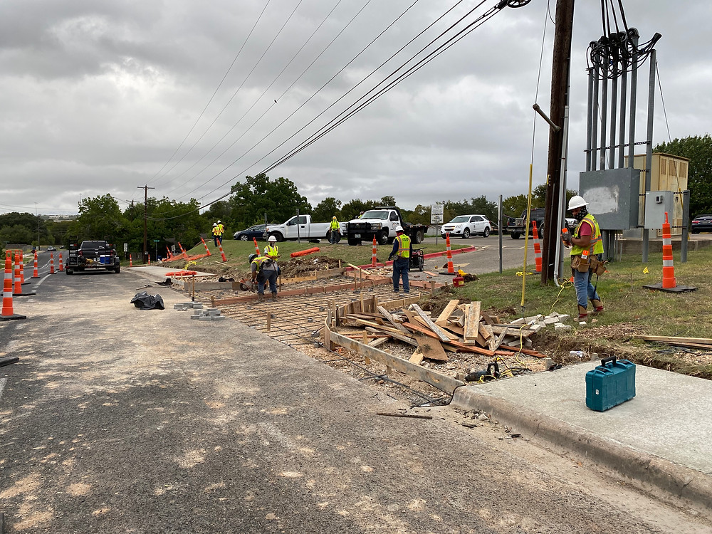 Construction workers setting up formwork and rebar in the right-of-way, specifically driveway and curbs, to receive concrete