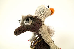 crochet weirdo character with two heads. contemporaray textile craft sculpture