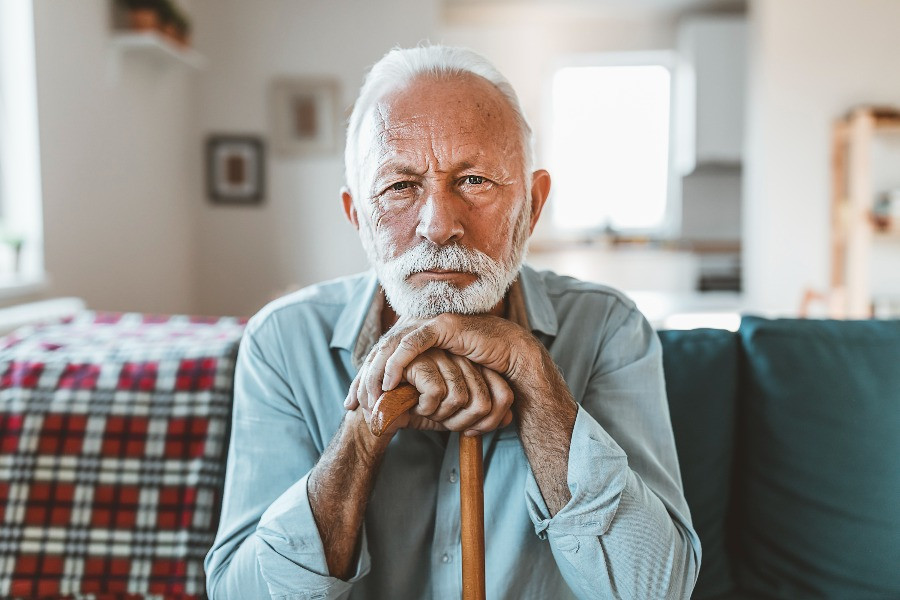 An eldery man sitting alone on his living room