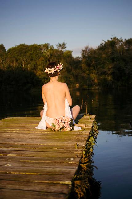 Nú na natureza. Mulher sentada em um pier. Do ensaio Boudoir
