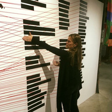 """Chandra interacts with the """"Kill the Indian, Save the Man"""" exhibit, in which black bars turn translucent when touched and reveal the names of U.S. Indian Boarding Schools that have been lost to history. Chandra has her hand on the boarding school Carlisle, where her great grandmother Elizabeth Bender and great uncle Charles Bender were sent. Piece by artist Ryan Feddersen."""