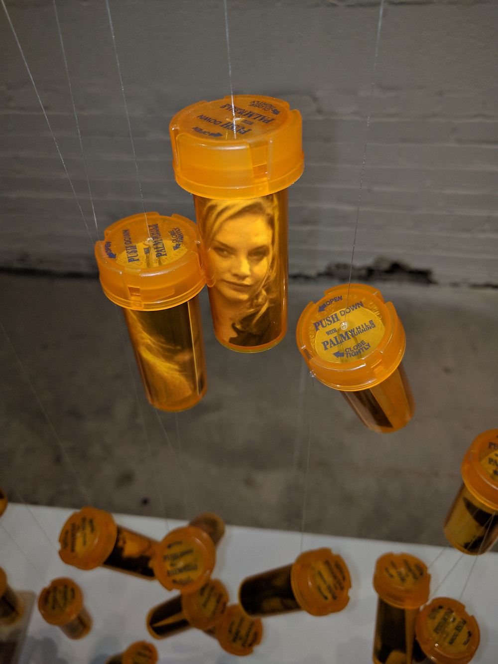 Commenting on the opoid crisis, this artists hung a pill bottle with a photo of celebreties who have overdosed.