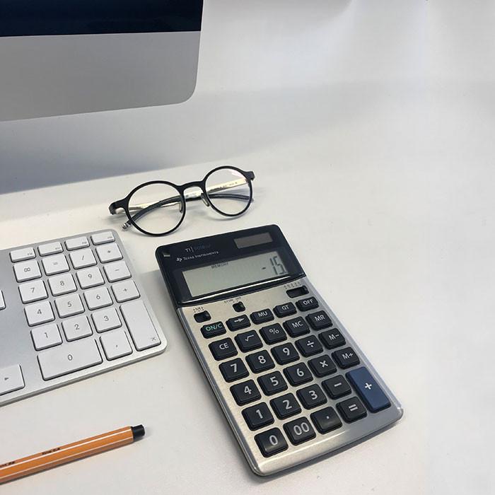 Rechner, Brille und Stift