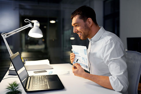 man smiling while looking at laptop screen