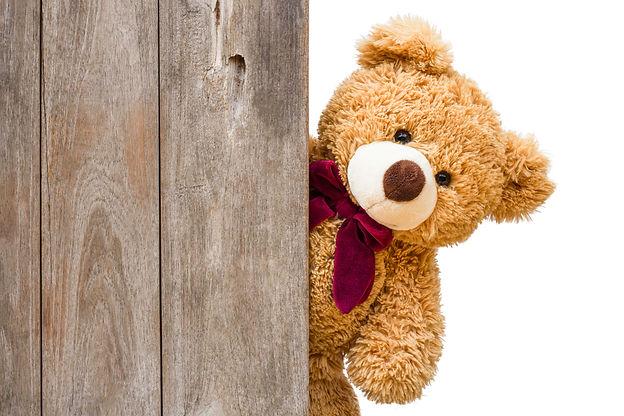 Brown cute teddy bear sneaked behind the