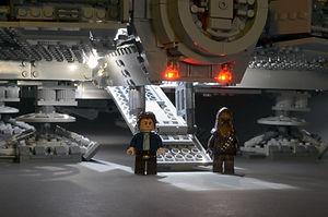 Han Solo and Chewbacca standing by the open boarding ramp of the LEGO UCS Millennium Falocn.