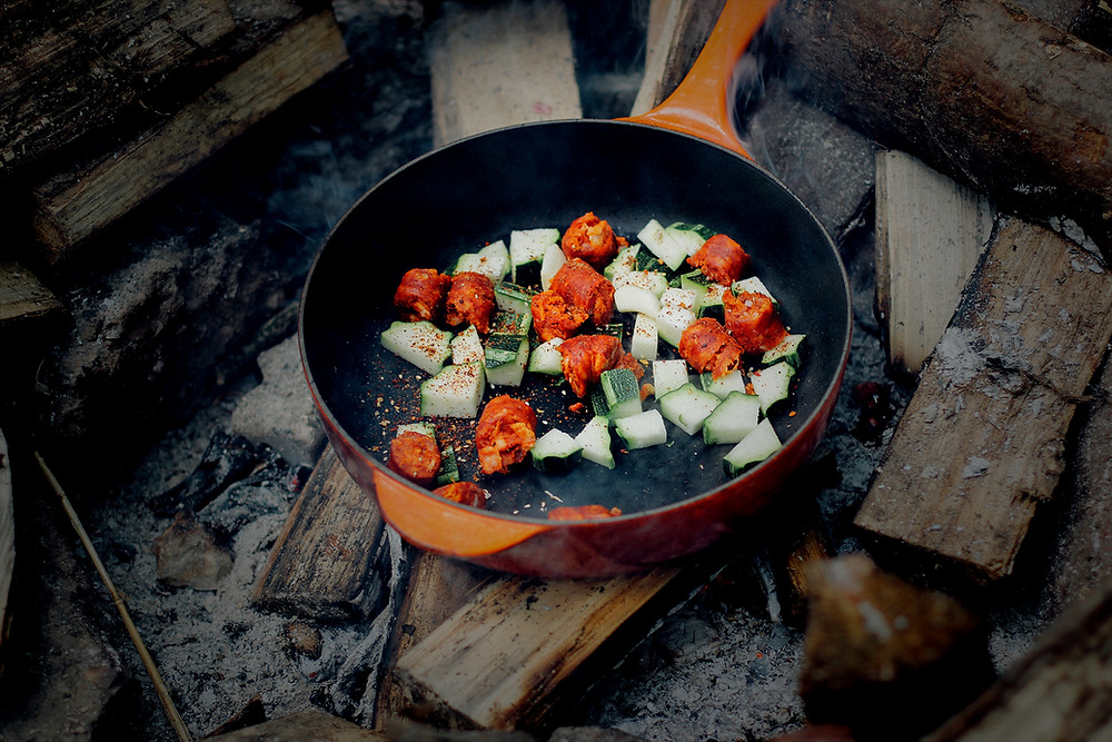 Skillet over campfire with cooking vegetables