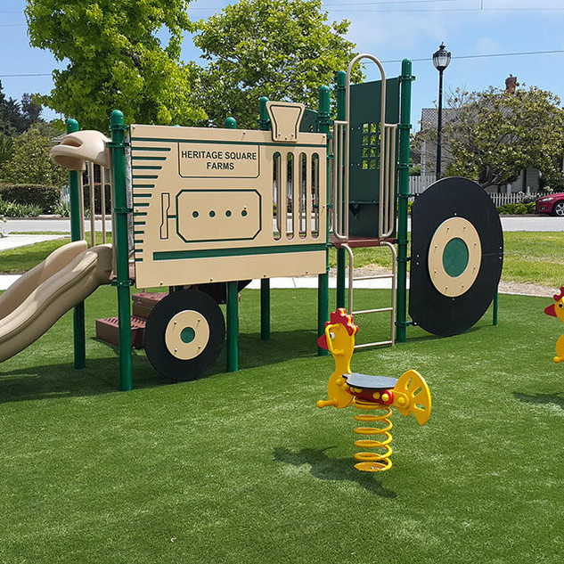 Completed project with playground equipment and fall area that looks like grass