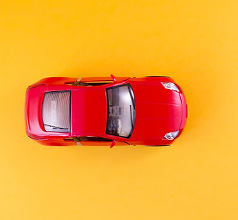 Toy red car on the yellow background top view_edited.jpg