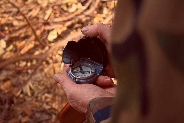 Jemand hält einen Kompass in den Händen, Waldboden im Hintergrund.