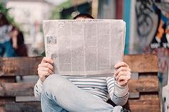 Jemand hält die aufgefaltete Zeitung in der Hand. Die Person ist hinter der Zeitung versteckt. Man sieht nur einen Streifen der Zeitung. Lesen was darin steht, kann man aber nicht.