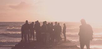 Ausschnitt aus dem Bild der Startseite: Die Büsten von Menschen, die im Abendlicht gegen das Meer schauen.