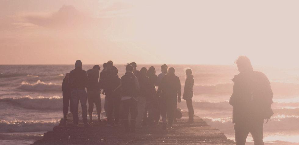 Menschen schauen im Abendlicht auf einem Steg Richtung Meer