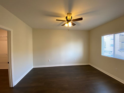 picture of bedroom with hard surface floors, ceiling fan, window with blinds and walk in closet