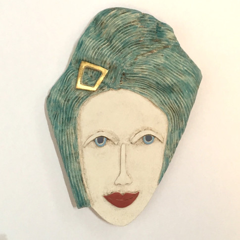 Curved earthenware ceramic face decorated with oxide and underglazes.  A small area has been embellished with 23.5 carat gold leaf. Hanger on the back for wall mounting. 20cm x 14cm x 1.5cm