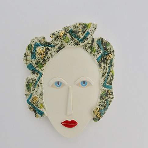 Curved earthenware ceramic face decorated with oxide, underglazes and glazes.  Some areas are embellished with 23.5 carat gold leaf.  Hanger on the back for wall mounting. 18cm x 14.5cm x 1.5cm