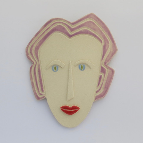 Curved stoneware ceramic face partially decorated with glazes.  Hanger on the back for wall mounting. 20cm x 15.5cm x 2cm