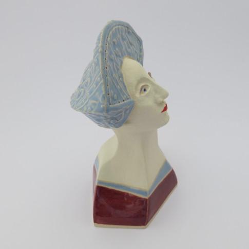 Earthenware figure decorated with underglazes and glazes. 14cm x 10.5cm x 7cm