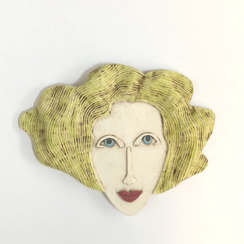 Curved earthenware ceramic face decorated with oxide and underglazes. Hanger on the back for wall mounting. 16cm x 20.5cm x 1.5cm