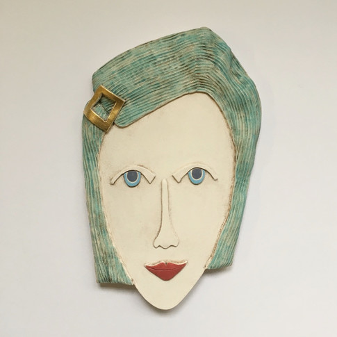 Curved earthenware ceramic face decorated with oxide and underglazes.  One area embellished with 23.5 carat gold leaf.  Hanger on the back for wall mounting. 25.5cm x 16cm x 2cm