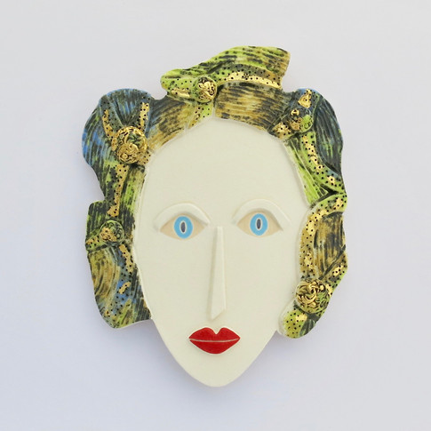Curved earthenware ceramic face decorated with copper oxide and underglazes.  Some areas are embellished with 23.5 carat gold leaf.  Hanger on the back for wall mounting. 18cm x 14.5cm x 1.5cm