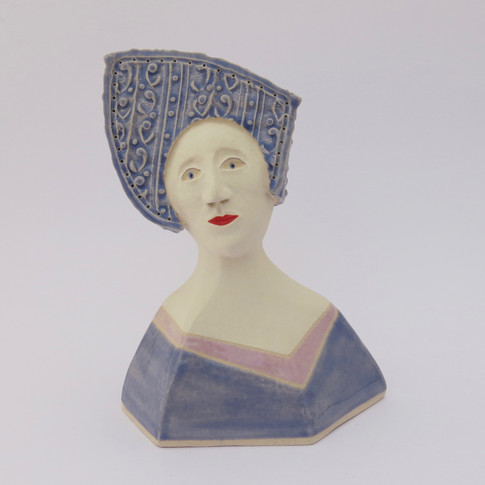 Earthenware figure decorated with underglazes and glazes. 13.5cm x 10.5cm x 7cm