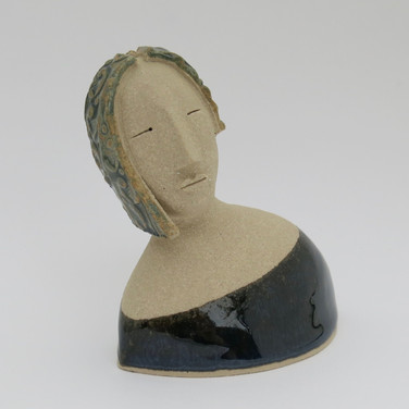 Stoneware figure partially decorated with glazes. 9cm x 9.5cm x 6cm