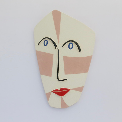 Curved earthenware ceramic face decorated with underglazes and glazes. Hanger on back for wall mounting. 21cm x 13cm x 2cm