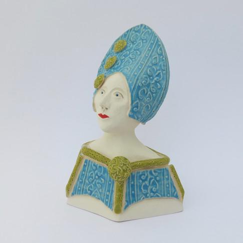 Earthenware figure decorated with underglazes and glazes. 15cm x 10.5cm x 7.5cm