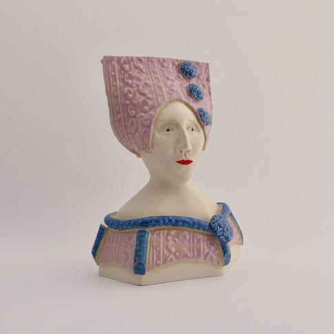 Earthenware figure decorated with underglazes and glazes. 14.5cm x 10.5cm x 7cm