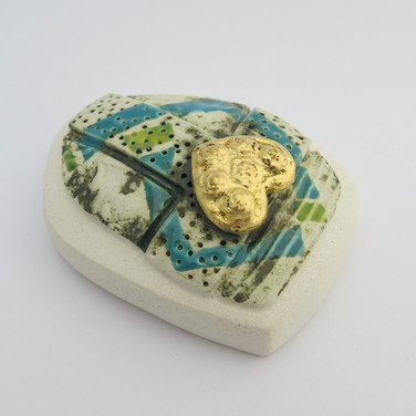 Earthenware hollow pebble decorated with copper oxide and glazes.  Heart is embellished with 23.5 carat gold leaf. 7cm x 5.5cm x 3.5cm