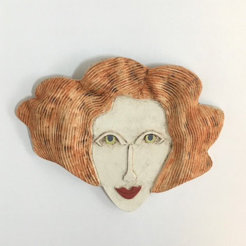 Curved earthenware ceramic face decorated with oxide and underglazes. Hanger on the back for wall mounting. 15.5cm x 20.5cm x 2cm