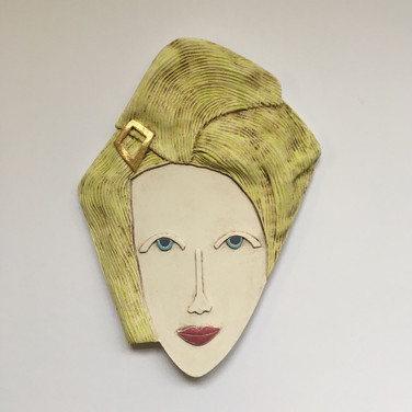 Curved earthenware ceramic face decorated with oxide and underglazes.  One area embellished with 23.5 carat gold leaf.  Hanger on the back for wall mounting. 26.5cm x 19cm x 2cm