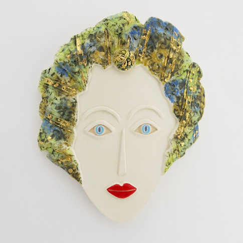 Curved earthenware ceramic face decorated with oxide and underglazes.  Some areas are embellished with 23.5 carat gold leaf.  Hanger on the back for wall mounting. 19cm x 15.5cm x 1.5cm