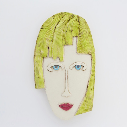 Curved earthenware ceramic face decorated with oxide and underglazes.  Hanger on the back for wall mounting. 24.5cm x 14.5cm x 2cm