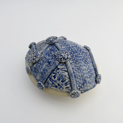 Stoneware hollow pebble partially decorated with cobalt oxide and clear glaze. 11.5cm x 10.5cm x 5.5cm