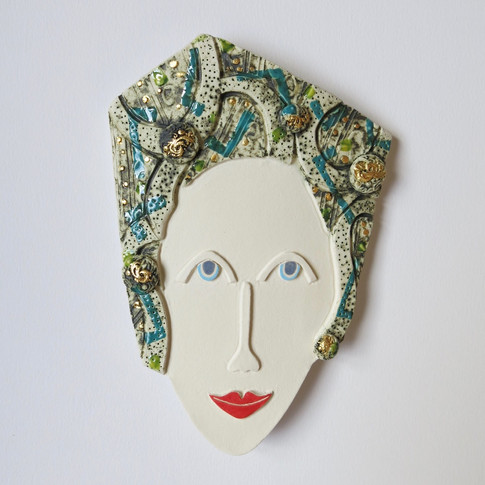 Curved earthenware ceramic face decorated with oxide, underglazes and glazes.  Some areas are further embellished with 23.5 carat gold leaf.  Hanger on the back for wall mounting. 22cm x 13cm x 2cm