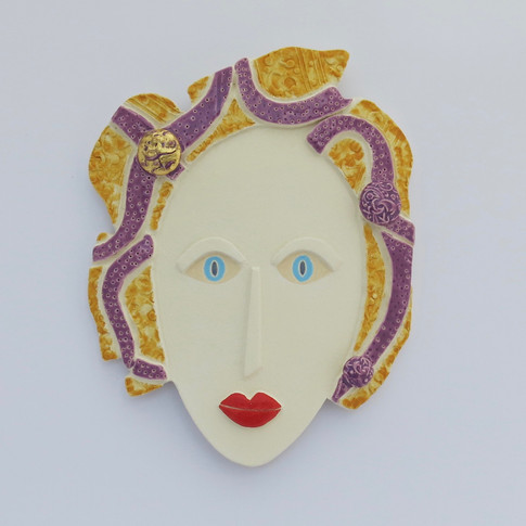 Curved earthenware ceramic face decorated with underglazes and glaze. A small area has been embellished with 23.5 carat gold leaf. Hanger on the back for wall mounting. 18cm x 14.5cm x 1.5cm