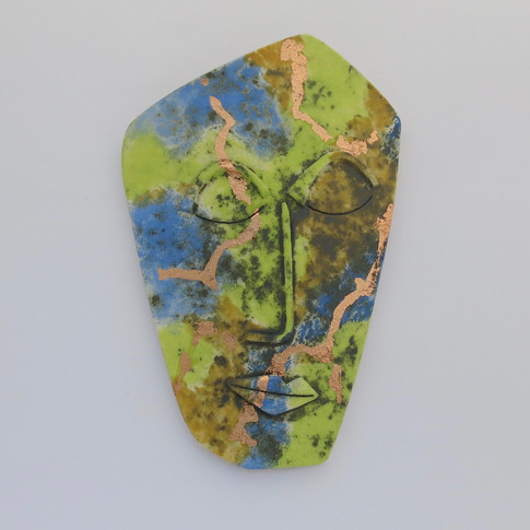 Curved eathenware ceramic face decorated with copper oxide, underglazes and copper foil. Hanger on the back for wall mounting. 20cm x 13cm x 2cm