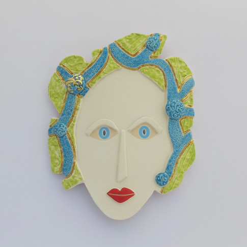 Curved earthenware ceramic face decorated with underglazes and glazes.  Some areas embellished with 23.5 carat gold leaf.  Hanger on the back for wall mounting. 18cm x 14.5cm x 1.5cm