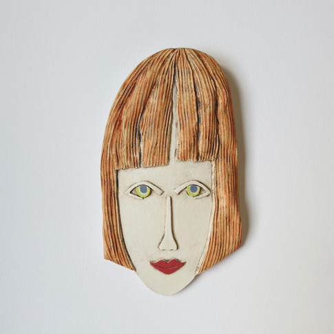 Curved earthenware ceramic face decorated with oxide and underglazes.  Hanger on the back for wall mounting. 21cm x 11.5cm x 2cm