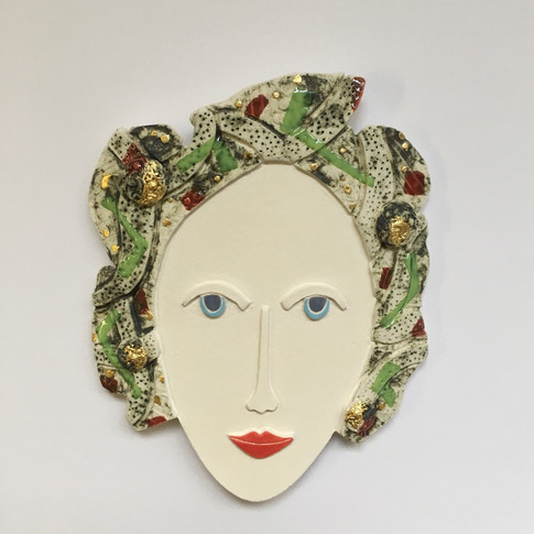 Curved earthenware ceramic face decorated with oxide, underglazes and glaze.  Some areas are embellished with 23.5 carat gold leaf.  Hanger on the back for wall mounting. 18cm x 14.5cm x 2cm