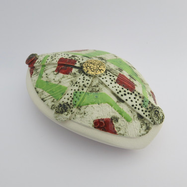 Earthenware hollow pebble partially decorated with copper oxide and glazes.  A small area is embellished with 23.5 carat gold leaf. 13.5cm x 9cm x 5cm