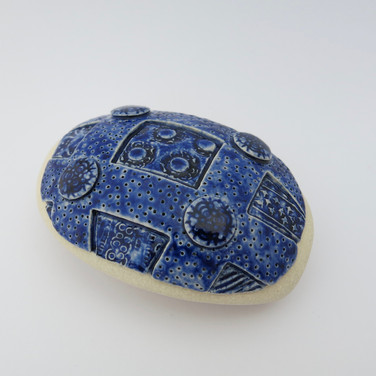 Stoneware hollow pebble partially decorated with cobalt oxide and clear glaze. 13cm x 9cm x 5cm