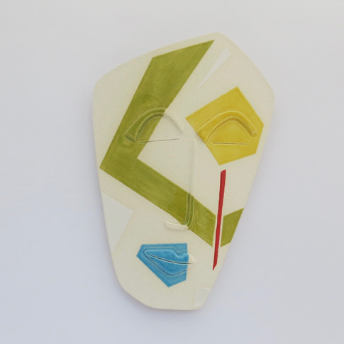 Curved earthenware ceramic face partially decorated with glazes.  Hanger on the back for wall mounting. 20cm x 15.5cm x 2cm