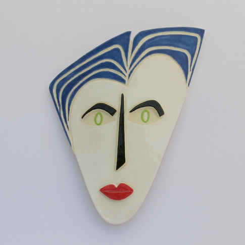 Curved earthenware ceramic face decorated with glazes.  Hanger on the back for wall mounting. 20cm x 16cm x 2.5cm