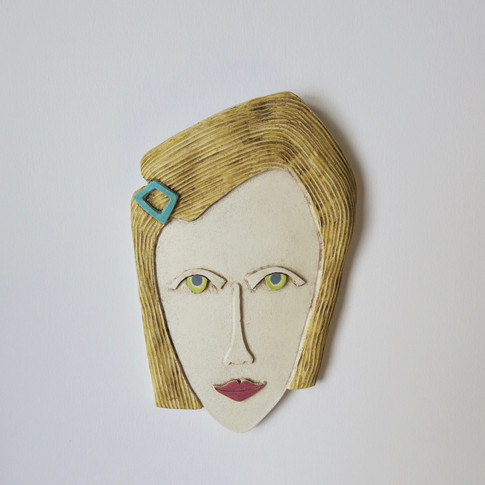 Curved earthenware ceramic face decorated with oxide and underglazes.  Hanger on the back for wall mounting. 21.5cm x 13cm x 2cm